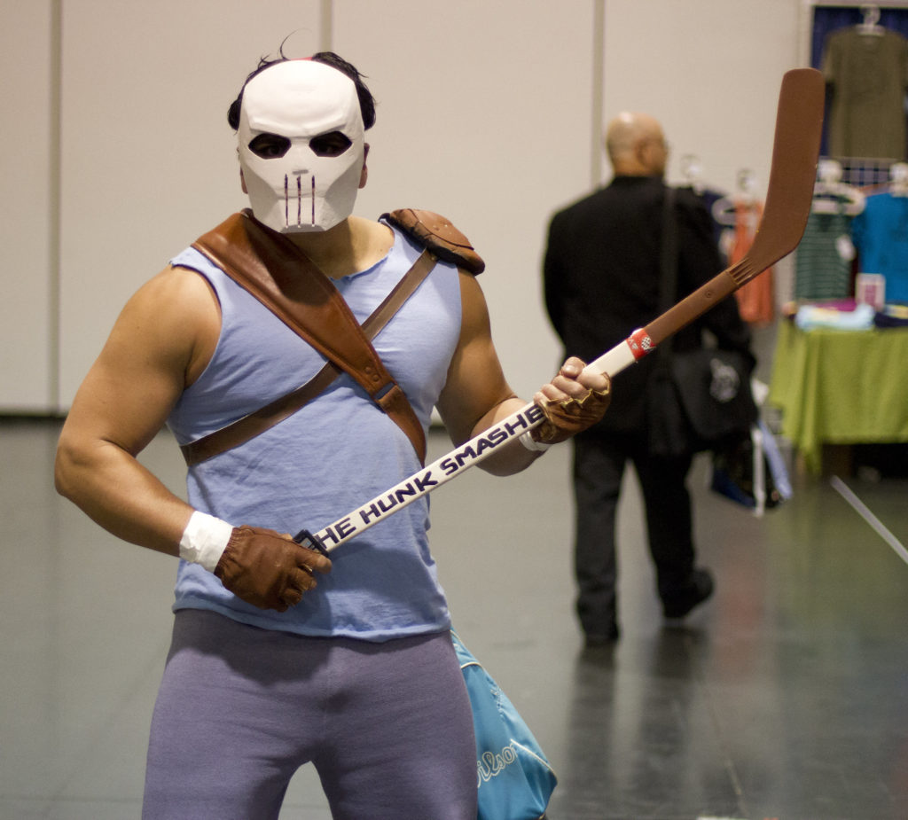 Casey Jones in blue sleeveless shirt and wears a full-face white mask