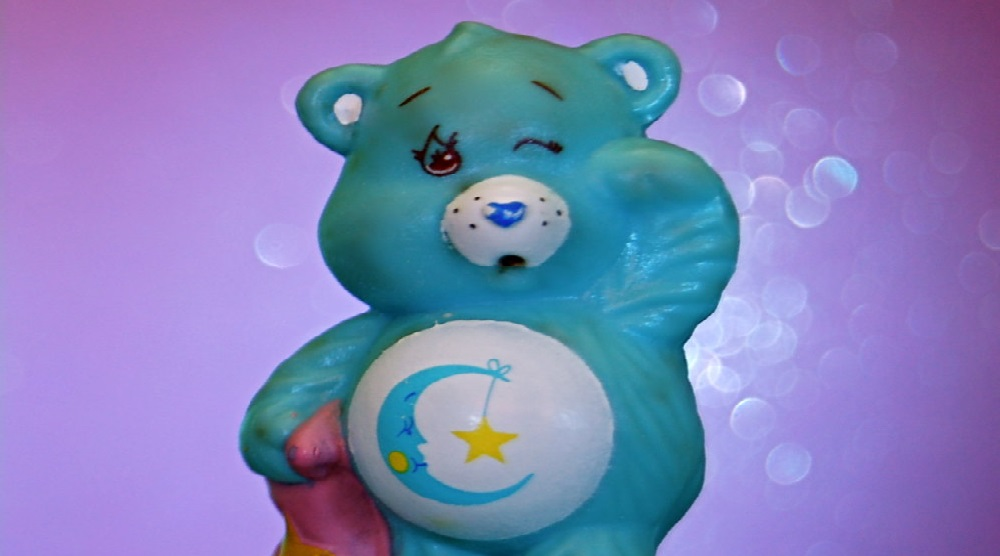 Aqua blue Care Bear named Bedtime Bear with a crescent moon and starssymbol on his tummy