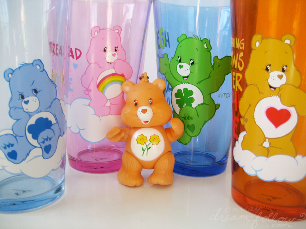 Friend Bear, the light-orange bear, with two smiling sunflowers on her tummy, with four Care Bear tumblers at the back