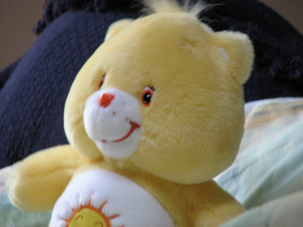 Funshine Bear, a yellow Care Bear, with a smiling golden sun on his tummy