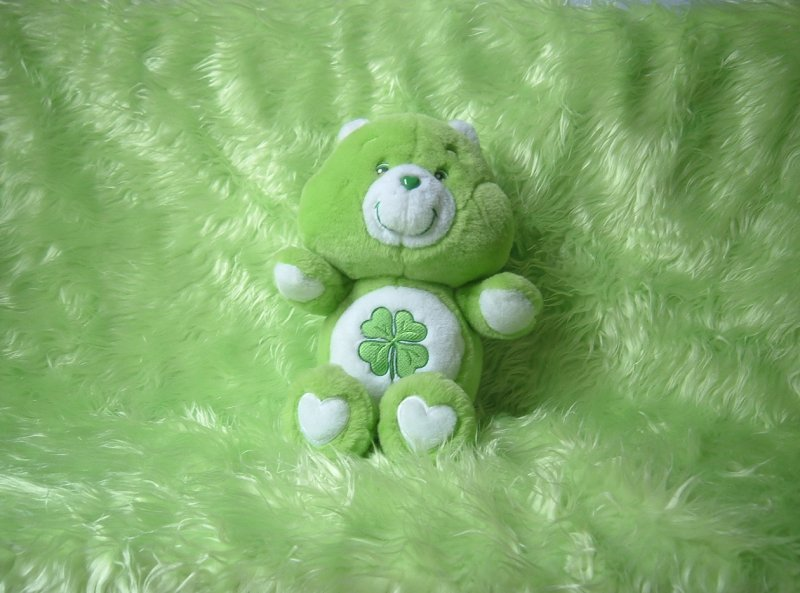 Good Luck Bear, the green Care Bear with a four-leaf clover on his tummy, with green faux feather background