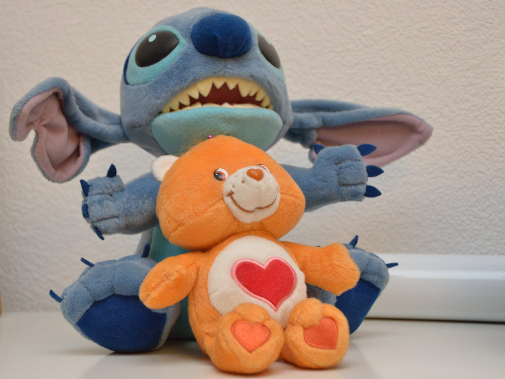 Tenderheart, an orange-brown Care Bear with a red heart with a pink outline on his tummy; on his back is a bigger Stitch stuffed toy