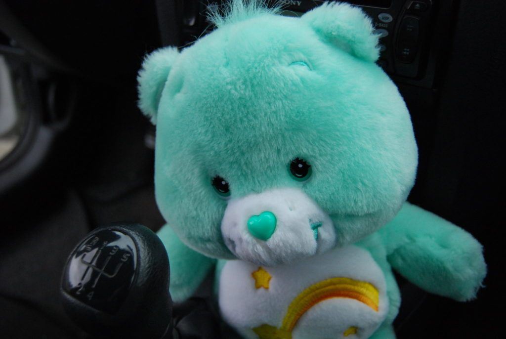 Teal Care Bear named Wish Bear inside a car; on her tummy is a smiling yellow shooting star with a gold comet tail surrounded by three other smaller stars