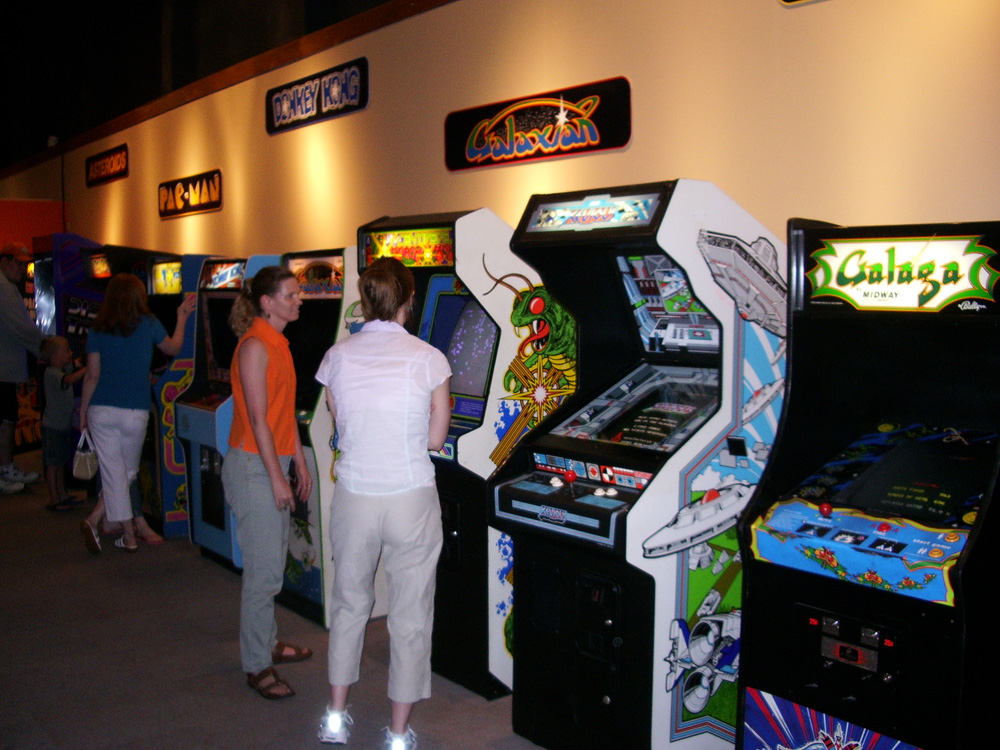 People playing stand up video games including Galaga