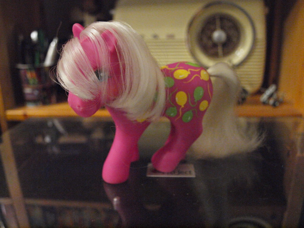 Pink Little Pony with side-swept blonde hair and green and yellow balloons on her hips
