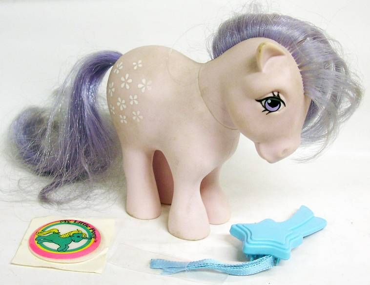 White Earth Pony in lavender-colored hair, tail, and eyes looking in a blue star toy on the floor