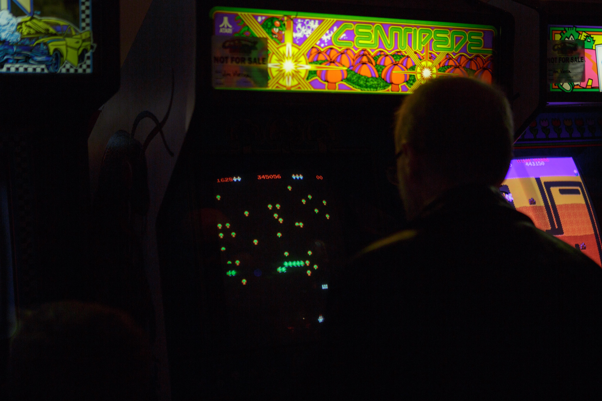 Someone playing Centipede in a dark arcade