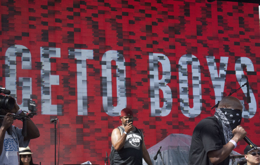 Geto Boys performing onstage with a large LED screen at the back
